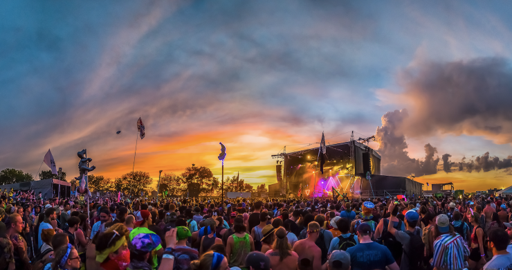 music festival stage and crowd at sunset