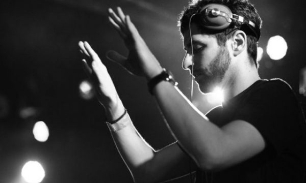Lane 8 puts hands in air with headphone on during a DJ set